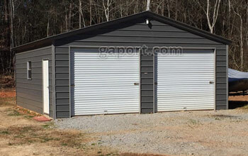 Tidy metal garage displaying use as a workshop with centered large door and entry door.