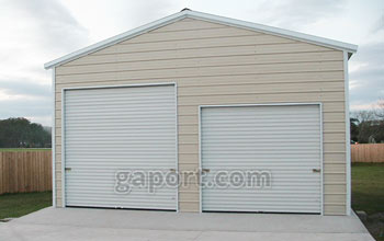 Tan garage with concrete slab base and two roll-up garage doors on the end.