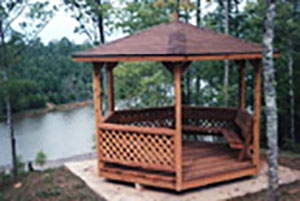At a lake side setting, an 8x8 round gazebo with a shingled roof.