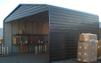Extra tall carport, parking or outdoor metal storage area shown with shelving inside. Notice support bracing.