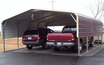 This picture shows a two car metal carport with round roof, brown siding and cream colored trim.