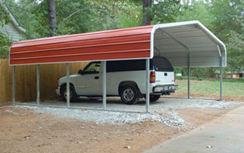 A popular rounded roof style red carport installed on gravel with room for SUV parking.