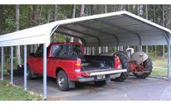Notice the standard metal carport with rounded roof shoing a truck and tractor parked neatly.