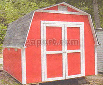 The photo shows a small portable red wood barn with an asphalt shingled roof.